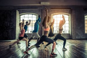 Group of people in a gym stretching before starting a workout session (Fitness Krazy)