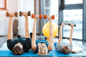 Happy family exercising with dumbbells at fitness studio. (Fitness Krazy)