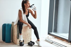 Woman drinking water after fitness training (lose weight)