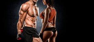very fit man and woman standing posing calisthenics