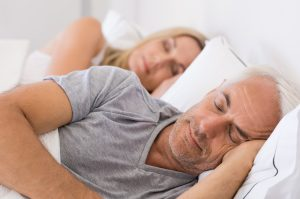 A couple sleeping in bed getting the rest required to feel fresh and energetic (Fitness Krazy Blog)