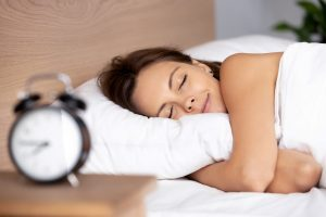 Woman in bed sleeping and getting some well deserved rest (Fitness Krazy Blog)