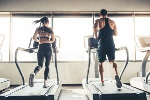 Back view of beautiful sports people running on a treadmill in gym. (Weight Loss Fitness Krazy)